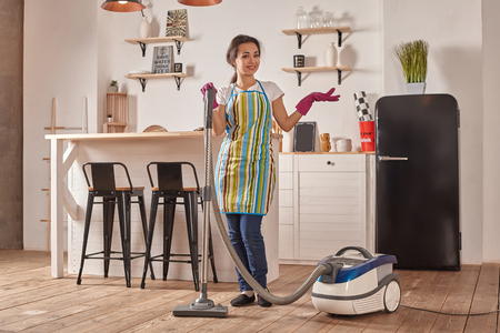 Young woman using vacuum cleaner in home kitchen floor, doing cleaning duties and chores, meticulous interior.