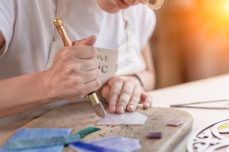 Künstler schneidet Buntglasplatten in kleine Mosaikquadrate. Nahansicht Standard-Bild
