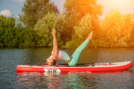 Young woman doing yoga on sup board with paddle. Yoga pose, side view - concept of harmony with the nature. 免版税图像