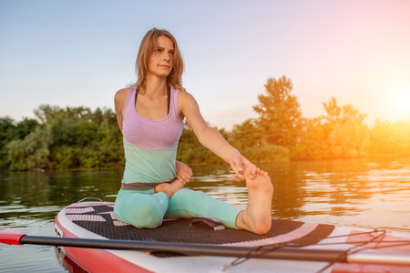 Young woman sitting on paddle board, practicing yoga pose. Doing yoga exercise on sup board, active summer rest