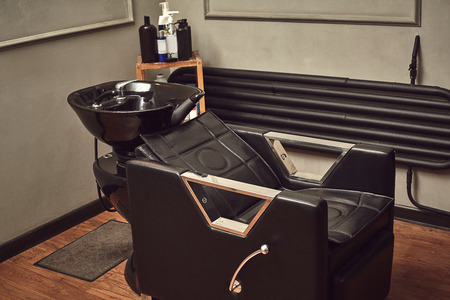 Black leather seat with wash basin in a barbershop interior with towels and shampoo on the side. Stock Photo