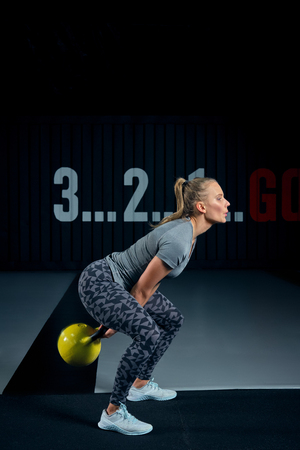 Young woman exercising with kettle bells at the gym.