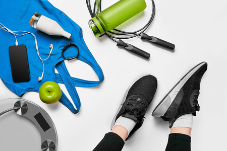 Sport woman sitting and resting after workout or exercise in fitness gym with protein shake or drinking water on floor. Relax concept. Flat lay