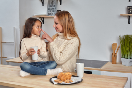Shot of cheerful mother and daughter sit together at kitchen table, drink hot tea in morning, have pleasant friendly talk between each other.