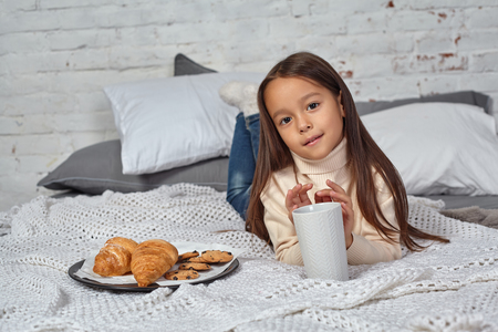 Pretty little girl 6 years old in a white sweater and jeans. Child in the room with a bed, eating croissant and drinking tea or cocoa.