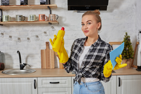 Professional young woman wearing rubber protective yellow gloves holding bottle cleaners in the kitchen. Фото со стока - 116221096