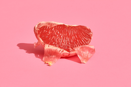 Half of grapefruit citrus fruit isolated on pink