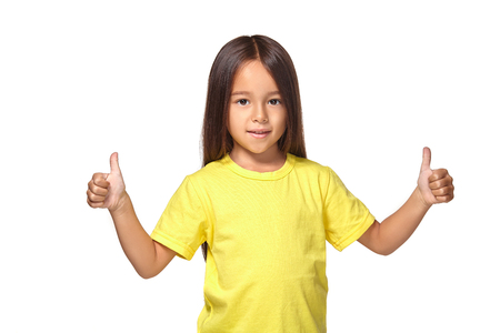 Girl in yellow t-shirt shows her hands with thumbs