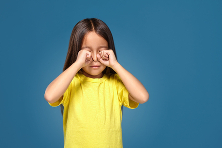 Sad offended little girl cries in yellow t-shirt