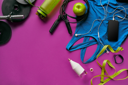 Health fitness background. Sneakers, dumbbell, power grip, green apple, water bottle, blue shirt, phone and earphone on dark background. Top view. Copy space
