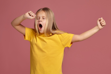 little girl in a yellow t-shirt. stretches and yawns