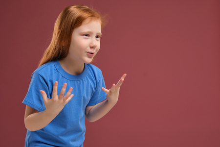 Portrait of cute redhead emotional little girl on red background