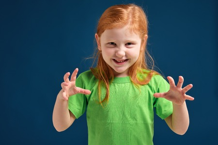 close up photo of little redhead emotional girl posing before camera on blue background 免版税图像