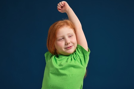 close up photo of little redhead emotional girl posing before camera on blue background Reklamní fotografie