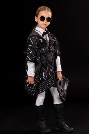 Little girl in a black glasses, dark poncho, black boots and a clutch in her hand Stock Photo