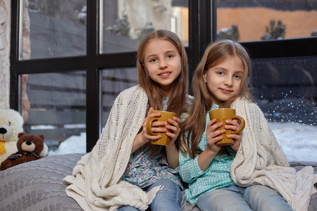 The image of two cute little sisters sitting on windowsill, covered by blanket. They drink warm tea