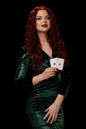 Sexy redheaded woman posing with a playing cards in her hands, on black background