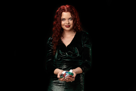 Sexy redheaded woman posing with a lot of chips in her hands, on black background