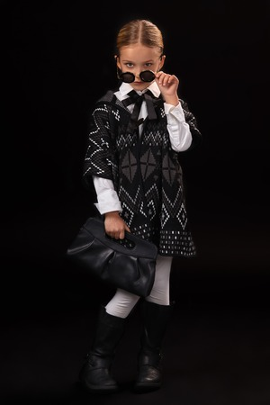 Little girl in a black glasses, dark poncho, black boots and a clutch in her hand