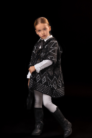 Little girl in a dark poncho, black boots and a clutch in her hand