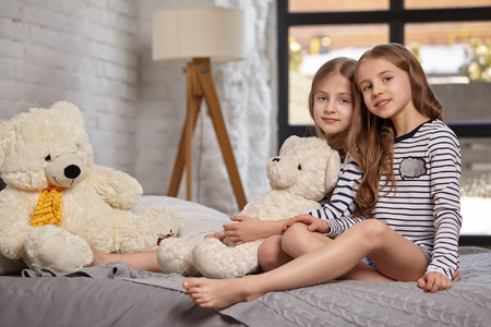 The image of two little sisters sitting on the bed in the room. 版權商用圖片