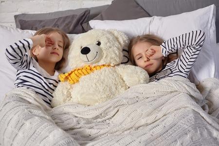 La imagen de dos hermanitas se despierta por la mañana.