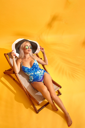 Beautiful young blonde woman in blue swimsuit lies on the lounger on yellow background