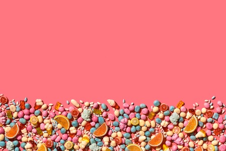 Various sweets, candys are palced on the photo on the coral background Imagens