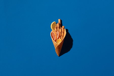 Wafer rolls and marmalade from waffle cone on blue background 版權商用圖片