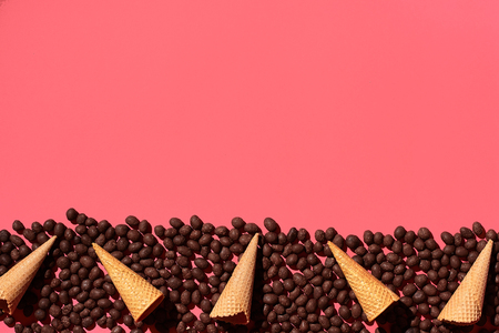 Chocolate dragee and waffle cones placed in fascinating order on coral background, view from above