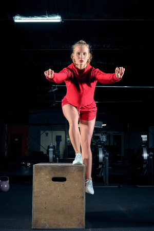 Female athlete is performing box jumps at gym.