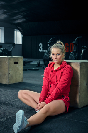 Young woman sitting near a box at gym after her workout and looking at the camera.