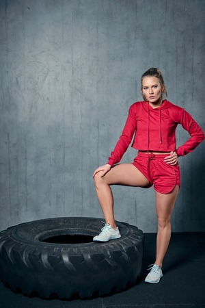 Powerful, attractive muscular girl engaged in gym, training with giant tires in the gym.