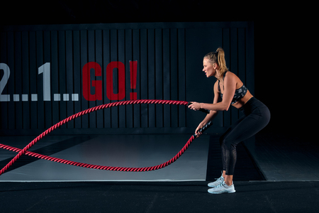 Athlete working out with battle ropes at cross gym. Фото со стока