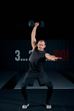 Strong brutal man doing squats with dumbbell at gym, full length photo. Guy doing exercises with dumbbell indoors.