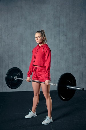 Attractive young sporty woman is working out in gym. Muscular woman is squatting with barbell