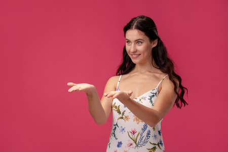 Portrait of a pretty young woman in a light dress standing on pink background in studio. People sincere emotions. Banque d'images