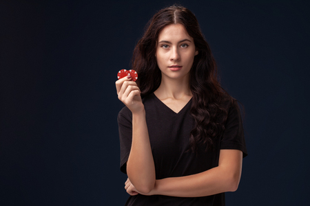 Curly hair brunette is posing with red gambling chips in her hands. Poker concept on a black background. Casino.