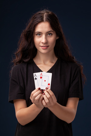 Close-up shot of curly hair brunette posing with playing cards in her hands. Poker concept on a black background. Casino. Imagens