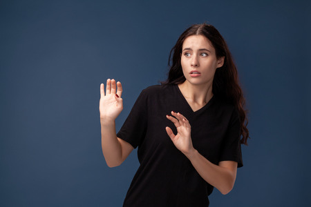 Portrait of a long-haired brunette woman in black t-shirt posing on a gray background and showing different emotions.