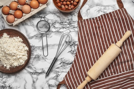 Close-up shot. Top view of a baking ingredients and kitchenware on the marble table background. Reklamní fotografie