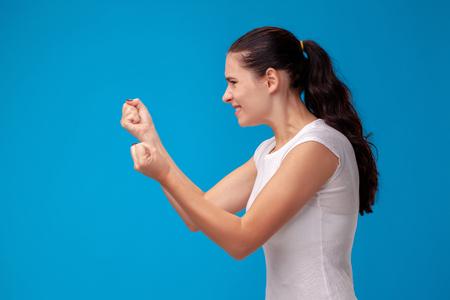 Studioporträt einer jungen schönen Frau in einem weißen T-Shirt gegen einen blauen Wandhintergrund. Menschen aufrichtige Emotionen. Standard-Bild
