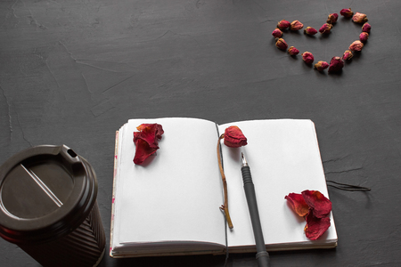 Top view of an empty notepad with dried rose and its petals on it, cup of coffee and a pen nearby, a heart made of a buds on a black background. Flat lay, copy space. Branding mockup.