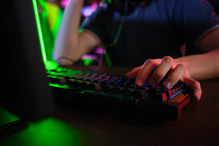 Close up view of professional players hands laying on gaming keyboard in gaming club or cyber arena
