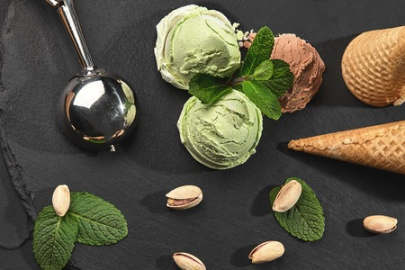 Top view of a chocolate and pistachio ice cream decorated with mint, waffle cones with scattered pistachios are nearby, served with a metal glossy scoop on a dark stone slate over a black background. Close-up. Archivio Fotografico - 122028588