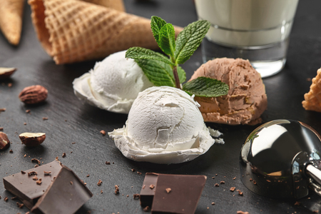 Top view of a homemade creamy and chocolate ice cream decorated with mint, a glass of milk, metal scoop, waffle cones with chocolate and hazelnuts nearby, served on a stone slate over a black backgrou