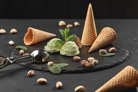 Appetizing chocolate and pistachio ice cream decorated with mint, waffle cones with scattered pistachios are nearby, served with a metal scoop on a stone slate over a black background. Close-up.