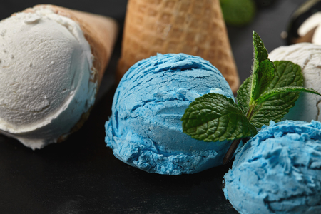 Close-up shot of a colorful creamy and blueberry ice cream decorated with fresh mint, and classic waffle cones are served on a stone slate standing on a dark table over a black background. Metal scoop is laying nearby.