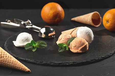 Close-up shot of a stone slate tray with a creamy and orange ice cream set decorated with fresh mint, and classic waffle cones on a dark table over a black background. Metal scoop is laying nearby. Summer coolness of ice cream and sorbet.