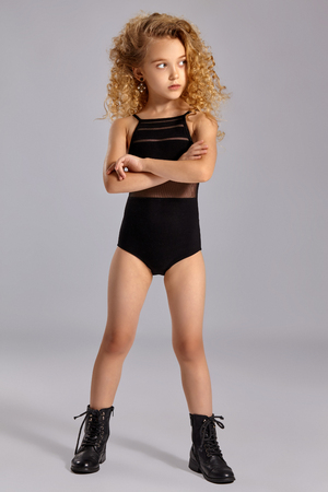 Beautiful little girl gymnast in a black sports swimsuit and boots on a gray background. 免版税图像